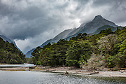 The Clinton River flows into Lake Te Anau at Glade Wharf under threatening clouds, at the start of the Milford Track in Fiordland National Park, Southland region, South Island of New Zealand. In 1990, UNESCO honored Te Wahipounamu - South West New Zealand as a World Heritage Area.