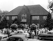 Auctioneer Donne pointed his cane to the successful bidder as he sold this brick apartment building at 603 E. 43rd St., on June 21, 1958 in a State Highway Department auction of buildings in the Seattle freeway path. (The Seattle Times archives)