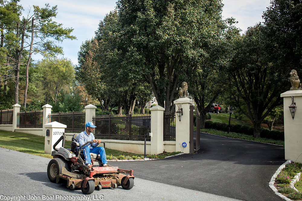 A groundskeeper passes by the gates of a home in Potomac Maryland, on Tuesday, September 26, 2017. Maryland's 6th District was redistricted in 2011, combining rural northern Maryland regions with more affluent communities like Potomac and Germantown. CREDIT: John Boal for The Wall Street Journal<br /> GERRYMANDER