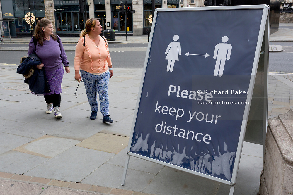 As the UK's Conornavirus pandemic lockdown continues, but with travel restrictions and social distancing rules starting to ease after three months of closures and isolation, two women disregard a large sign asking for social distancing outside Charing Cross station, on 9th June 2020, in London, England.