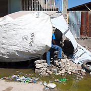Haitian families live in the public roadways after gathering whatever they can to build their homes. Running water is polluted with contaminants but is still used for personal hygiene and drinking..Mandatory Credit: Alex Menendez Dwight Howard in Haiti after the 2010 earthquake for the D12 Foundation relief fund.