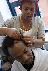 Hairdresser giving a demonstration at her stand at Nottingham's 'Women's Enterprise Day' exhibition; held at the New Deal for Communities centre,