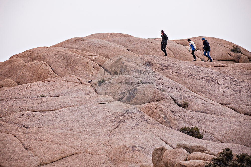 Hikers walk along Jumbo Rocks in Joshua Tree National Park, California.