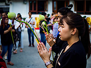 """01 MARCH 2018 - BANGKOK, THAILAND:  People pray at Wat Pathum Wanaram in central Bangkok. Many people go to temples to perform merit-making activities on Makha Bucha Day, which marks four important events in Buddhism: 1,250 disciples came to see the Buddha without being summoned, all of them were Arhantas, or Enlightened Ones, and all were ordained by the Buddha himself. The Buddha gave those Arhantas the principles of Buddhism. In Thailand, this teaching has been dubbed the """"Heart of Buddhism.""""    PHOTO BY JACK KURTZ"""