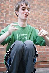 Teenage boy with Autism playing in backyard,