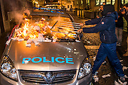 A police car is attacked and set on fire near Scotland Yard - The annual Million Mask March bonfire night protest started in Trafalgar Square and headed to Westminster where it splintered. The march was organised by Anonymous UK and marchers wore the trademark V for Vendetta, Guy Fawkes masks. The police had placed tight restrictions on the route after trouble last year but, after a brief kettle, seemed happy to let the crowd filter in different directions.