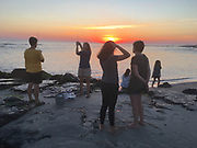 Family gathers on Cape May Point beach at sunset,