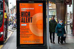 © Licensed to London News Pictures. 10/12/2020. London, UK. People walk past 'Coronavirus Tier 2 High Alert' public information campaign digital poster in north London amid fears of London going into tougher lockdown restrictions as early as next week. According to Public Health England, 24 of the London's 32 boroughs recored a rise in infections one week after second lockdown. Photo credit: Dinendra Haria/LNP