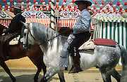 """Riders, men and women dress up in their finery, the traditional """"traje corto"""" (short jacket, tight trousers and boots) for men. The men traditionally wear hats called """"cordobés"""". Passing casetas behind..The Feria de abril de Sevilla, """"Seville April Fair"""" dates back to 1847. During the 1920s, the feria reached its peak and became the spectacle that it is today. It is held in the Andalusian capital of Seville in Spain. The fair generally begins two weeks after the Semana Santa, Easter Holy Week. The fair officially begins at midnight on Monday, and runs six days, ending on the following Sunday. Each day the fiesta begins with the parade of carriages and riders, at midday, carrying Seville's citizens to the bullring, La Real Maestranza...For the duration of the fair, the fairgrounds and a vast area on the far bank of the Guadalquivir River are covered in rows of casetas (individual decorated marquee tents which are temporarily built on the fairground). Some of these casetas belong to the prominent families of Seville, some to groups of friends, clubs, trade associations or political parties. From around nine at night until six or seven the following morning, at first in the streets and later only within each caseta, crowds of people party and dance Sevillanas, traditional Flamenco dances, Sevillan style drinking Jerez sherry, or Manzanilla wine, and eating tapas."""