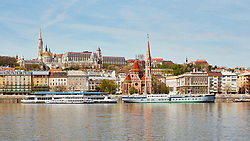 Matthias Church and Reformed church with docked ship on Danube river, Budapest, Hungary