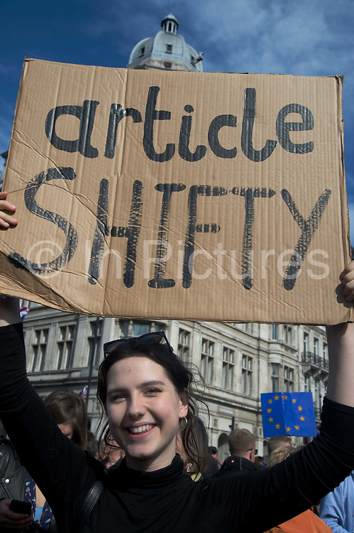Hundreds of thousands of people protest in the Unite for Europe March on Parliament against Brexit demonstration on 25th March 2017 in London, United Kingdom. The march in the capital brings together protesters from all over the country, angry at the fact that Article 50 will be invoked and to listen to the 48 percent of British voters who voiced against Brexit. Since the vote was announced, there have been demonstrations, protests and endless political comment in all forms of media. Half of the country very displeased with the result and the prospect of being taken out of the European Union against their will, and with uncertainty as to what will happen next in the politics surrounding the exit from Europe. A young woman holds a cardboard sign saying Article shifty, satirising Article Fifty.