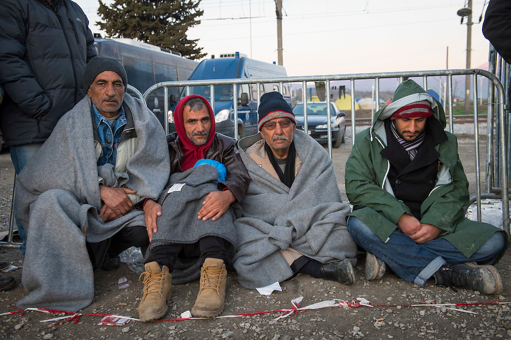March 5, 2016 - Idomeni, Greece: Man wait in the early morning for registration for a border crossing to open in make shift camp at the  Idomeni border crossing in Greece. 13,000 refugees are stuck here after Macedonia closed the border. New arrivals come in every day, making living conditions more and more difficult, so that the local government asked the emercency state was declared . (Steven Wassenaar/Polaris)