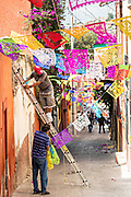 Workers string papel picado banners across an alley in preparation for a Dead of the Dead procession during the Dia de Muertos festival in San Miguel de Allende, Mexico. The multi-day festival is to remember friends and family members who have died using calaveras, aztec marigolds, alfeniques, papel picado and the favorite foods and beverages of the departed.