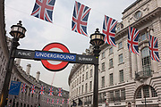 British flags hang along Londons Regent Street with the London Underground sign at its Piccadilly Circus station on 7th June 2016. The angle is looking up at the curved architecture created by John Nash in the 18th century but which still dominates the capitals West End known for luxury consumer brands. Regent Street is named after the Prince Regent later George IV and associated with architect Nash, whose street layout survives. The street was completed in 1825 and was an early example of town planning in England, cutting through the 17th and 18th century street pattern through which it passes.