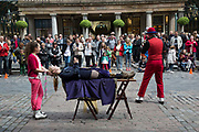 Street performer in Covent Garden delighting the gathered crowds with his levitation trick with a member of the public from the gathered crowd. Balanced on two chairs, one is removed. London, UK.
