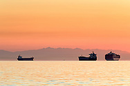 Cargo ships anchored in English Bay at sunset with the mountains of Vancouver Island in the background.  Photographed from Ambleside Beach Park in West Vancouver, British Columbia, Canada.