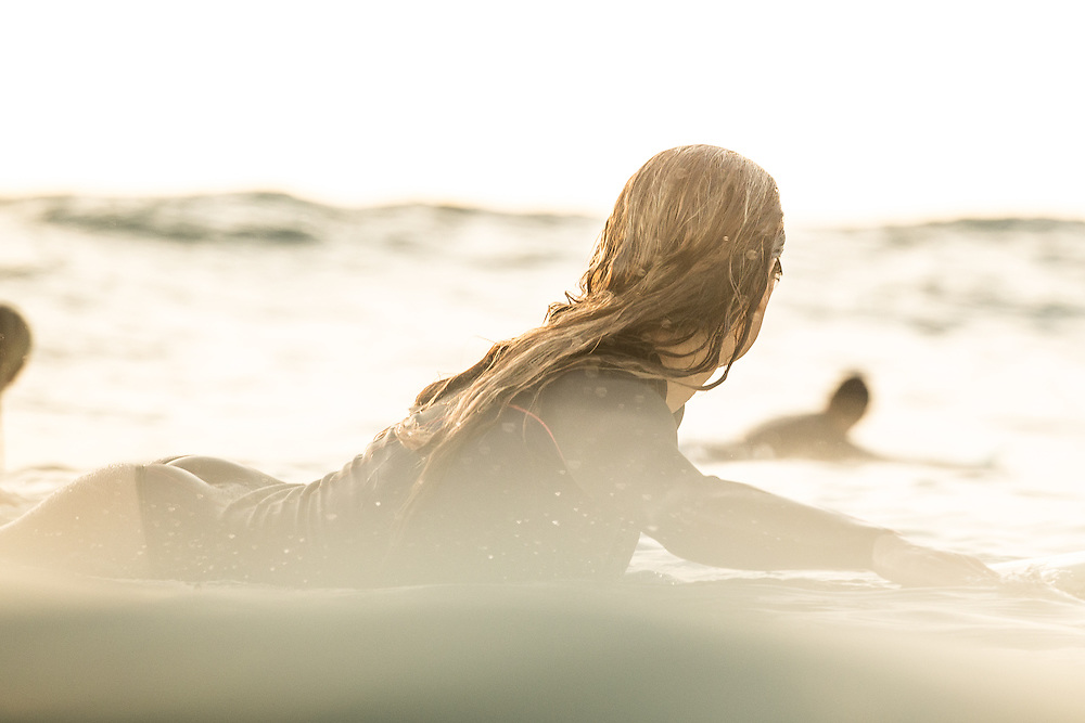 Surfer girl going for a wave in Mission Beach, San Diego, CA.