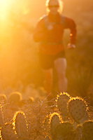 A young woman trail running at sunset in Sedona, Arizona.