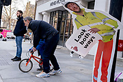 Waiting for a green light to cross the road, an adult man guides a young boy on his bike, alongside a construction industry warning sign, erected to warn pedestrians, but damaged so that it is seemingly bending over at the waist, on 8th March 2021, in London, England.
