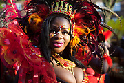 A young woman dressed up in red feathers smiles in the sun.The Notting Hill Carnival has been running since 1966 and is every year attended by up to a million people. The carnival is a mix of amazing dance parades and street parties with a distinct Caribbean feel.