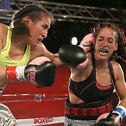"""Noemi Bosques (R) throws a right hand against Nydia Feliciano""""s left hook during a Telemundo Boxeo boxing match at the A La Carte Pavilion on Friday,  March 13, 2015 in Tampa, Florida.  Feliciano won the bout by split decision. (AP Photo/Alex Menendez)"""