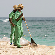 Resort walkers raking up garbage on the beach in Punta Cana