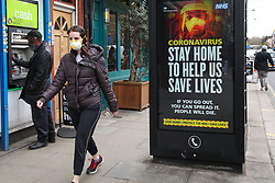 © Licensed to London News Pictures. 02/04/2020. London, UK. A woman wearing a face mask walks past a coronavirus public information campaign poster in north London, which focuses on 'STAY HOME TO HELP US SAVE LIVES' as coronavirus lockdown continues. Photo credit: Dinendra Haria/LNP