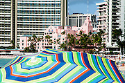 A colorful beach umbrellain Waikiki with the Royal Hawaiian Hotel in the background.