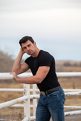good looking man leaning on a ranch fence