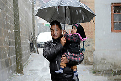 A Kashmiri man walks along with his daughter holding umbrella amid snowfall in Srinagar, the summer capital of Indian controlled Kashmir. Kashmir witnessed its first snowfall.