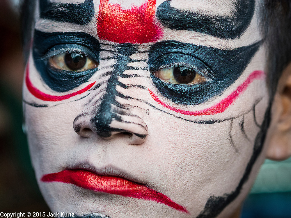 """14 MAY 2015 - BANGKOK, THAILAND:    A Chinese opera performer backstage before a show at the Pek Leng Keng Mangkorn Khiew Shrine in the Khlong Toey slum in Bangkok. Chinese opera was once very popular in Thailand, where it is called """"Ngiew."""" It is usually performed in the Teochew language. Millions of Chinese emigrated to Thailand (then Siam) in the 18th and 19th centuries and brought their culture with them. Recently the popularity of ngiew has faded as people turn to performances of opera on DVD or movies. There are still as many 30 Chinese opera troupes left in Bangkok and its environs. They are especially busy during Chinese New Year and Chinese holiday when they travel from Chinese temple to Chinese temple performing on stages they put up in streets near the temple, sometimes sleeping on hammocks they sling under their stage. Most of the Chinese operas from Bangkok travel to Malaysia for Ghost Month, leaving just a few to perform in Bangkok.    PHOTO BY JACK KURTZ"""