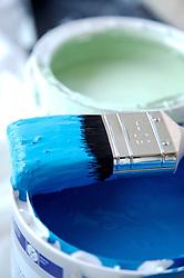 Close up of blue paint pot and paintbrush
