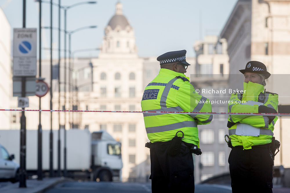 The morning after the terrorist attack at Fishmongers Hall on London Bridge, in which Usman Khan (a convicted, freed terrorist) killed 2 during a knife a attack, then subsequently tackled by passers-by and shot by armed police - officers guard the southern end of the bridge, on 30th November 2019, in London, England.