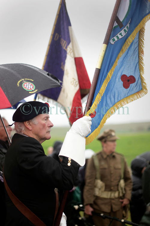 11 November 2018. Lochnagar Crater, La Boisselle, Somme, France. <br /> <br /> Royal Engineer Vinny Felsdead holding a commemorative flag. <br /> <br /> Gathered in the pouring rain, those who perished in the Great War are remembered by British and French civilians on the 100th anniversary of the Great War. <br /> <br /> Lochnagar Crater was created by the Tunnelling Companies of the Royal Engineers under a German field fortification. The explosion was the loudest man made noise created at that time, purportedly heard in London. <br /> <br /> Photo©; Charlie Varley/varleypix.com