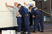 28 JANUARY 2010 -- BUCKEYE, AZ: Undocumented immigrant inmates are searched and handcuffed by ICE officers before boarding an ICE bus at Lewis Prison. The Arizona Department of Corrections transferred 51 undocumented immigrant inmates from state control to the Immigration and Customs Enforcement at Lewis Prison in Buckeye Thursday morning. The inmates have less than 90 days left on their sentences and will be deported to their countries of origin when they finish their prison terms.  PHOTO BY JACK KURTZ