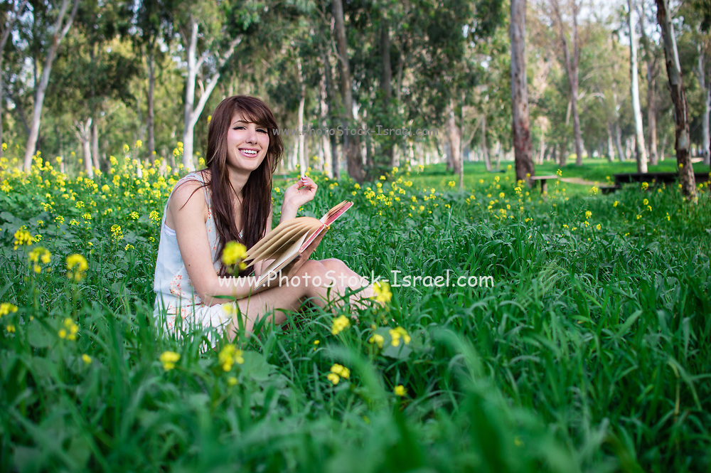 Young smiling middle eastern woman reads a book in a park