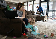 Beth Bond tries to work from home while entertaining her daughter Mady, 6, and her husband Lee Madsen feeds daughter James, 9 months, on Tuesday, March 17, 2020 at their River North apartment during the coronavirus pandemic. (Brian Cassella/Chicago Tribune)