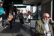 Street Scene on Piccadilly in London, England, United Kingdom. A well dressed gentleman in a tweed jacket waits at a bus stop in the sunshine.