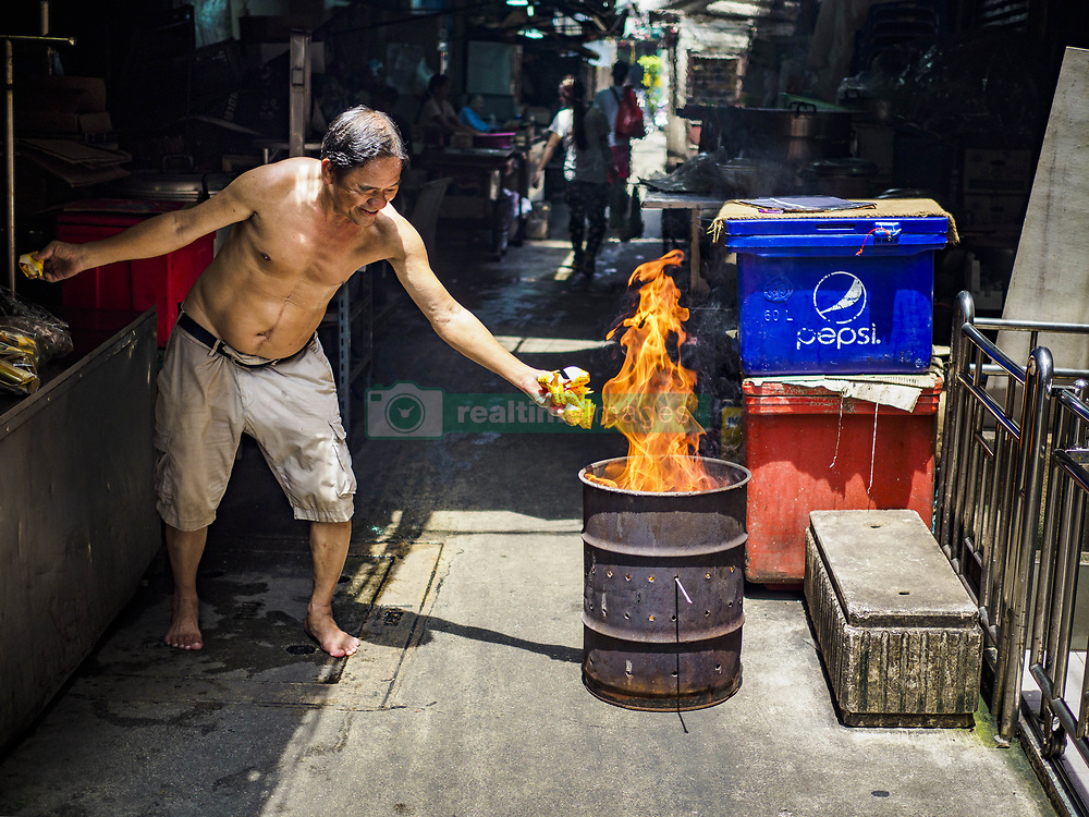 September 5, 2017 - Bangkok, Thailand - A man in Bangkok's Chinatown burns ghost money on Hungry Ghost Day. The Ghost Festival is a Buddhist and Taoist holy day celebrated on the 15th day of the 7th lunar month. It is primarily celebrated in China and Chinese communities outisde China. In Thailand, it's celebrated in Thai-Chinese communities in Bangkok, Phuket and Chiang Mai.  On that day ghosts and spirits, including those of the deceased ancestors, come out from the lower realm to visit the living. Families prepare elaborate banquets for the spirits and burn 'ghost money' for the spirits to use in the other realm. It is a day for venerating dead relatives. (Credit Image: © Jack Kurtz via ZUMA Wire)