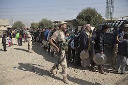 November 11, 2016 - Mosul, Nineveh, Iraq - Iraqi refugees, who have escaped fighting in Mosul, queue for lunch outside a mosque, where many are temporarily staying, in the city's Hay Intisar district on the south east of the city. The district was taken by Iraqi Security Forces (ISF) around a week ago and, despite its proximity to ongoing fighting between ISF and ISIS militants, many residents still live in the settlement. (Credit Image: © Matt Cetti-Roberts via ZUMA Wire)