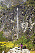 Hikers take lunch in front of waterfall by Rob Roy Glacier, Mt. Aspiring National Park, South Island, New Zealand