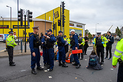 """© Licensed to London News Pictures. 27/10/2021. London, UK. Police officers holding tool kits stand next to protesters from climate campaign 'Insulate Britain', an offshoot of Extinction Rebellion (XR), as they block traffic on the A40 Western Avenue in Acton. Following a national injunction covering England's highways, Insulate Britain declared the M25 """"a site of nonviolent civil resistance"""" vowing to return to the motorway network to continue their protest action. Photo credit: Peter Manning/LNP"""