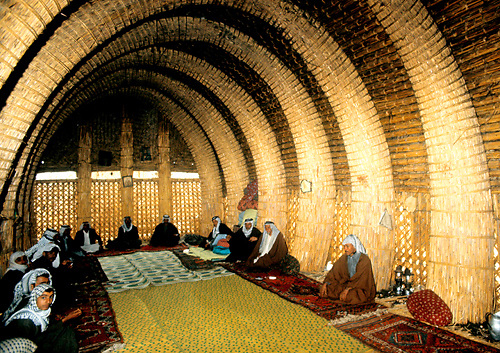 Iraqi marshmen sit in the interior of elaborate mudhif guest house made of reeds and rush mats in a Marsh Arab village in the marshlands of Southern Iraq where the Tigris and Euphrates meet