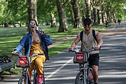A girl who revealed her breast and raised two fingers (V for victory or freedom) is seen cycling with a friend along London's Hyde Park on Friday, May 15, 2020. (Photo/ Vudi Xhymshiti)