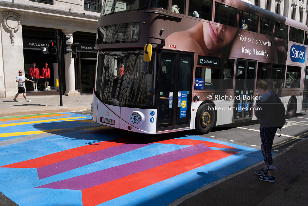 A number 12 bus adorned with an ad for skincare brand Sanex, drives over the multi-coloured markings of a crossing at Lower Regent Street, on 16th July 2021, in London, England.
