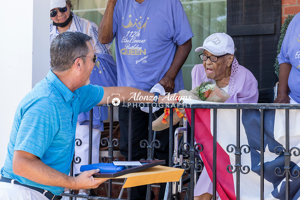 Oklahoma State Senator Chuck Hall, left, of district 20 greets and presents Ethel M. Bowens, center, with flowers and gifts during a celebration parade in Guthrie, Okla. outside of the Golden Age Nursing Home in honor of her 112th birthday and being named the oldest living Oklahoman on Saturday, Aug. 21, 2021. Photo by Alonzo J. Adams.