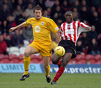 Picture: Henry Browne.<br /> Date: 26/12/2003.<br /> Brentford v Bristol City Nationwide League Division 2.<br /> Lee Peacock of City and Brentford's Joel Kitamirike battle for the ball.