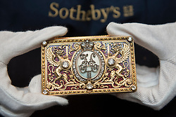"""© Licensed to London News Pictures. 01/06/2018. LONDON, UK. A Sotheby's technician presents """"An Imperial Presentation Fabergé jewelled gold and enamel box"""", 1897, by Michael Perchin (Est. GBP150-200k) at a preview of the Russian Pictures and Russian Works of Art, Fabergé & Icons sale which will take place at Sotheby's, New Bond Street on 5 June.  Photo credit: Stephen Chung/LNP"""