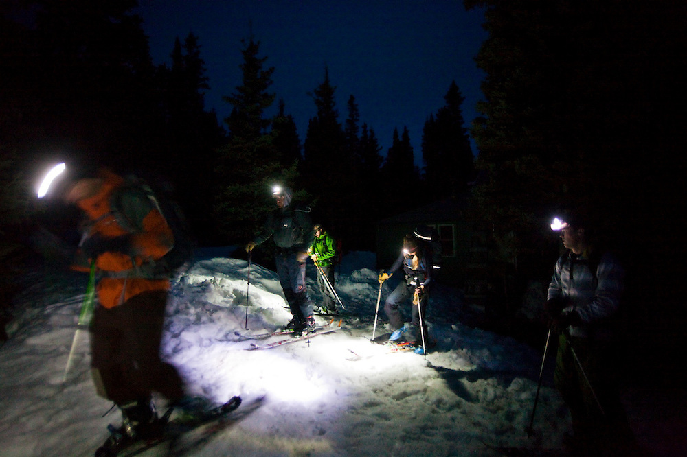 Backcountry skiers gather with their headlamps at dawn outside the Ridgway Hut, San Juan Mountains, Colorado.