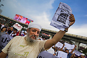 """25 MAY 2014 - BANGKOK, THAILAND: A Thai-Indian carries a """"wanted"""" poster with a picture of Gen. Prayuth Chan-ocha, leader of the coup that unseated the elected civilian government. Public opposition to the military coup in Thailand grew Sunday with thousands of protestors gathering at locations throughout Bangkok to call for a return of civilian rule and end to the military junta.     PHOTO BY JACK KURTZ"""